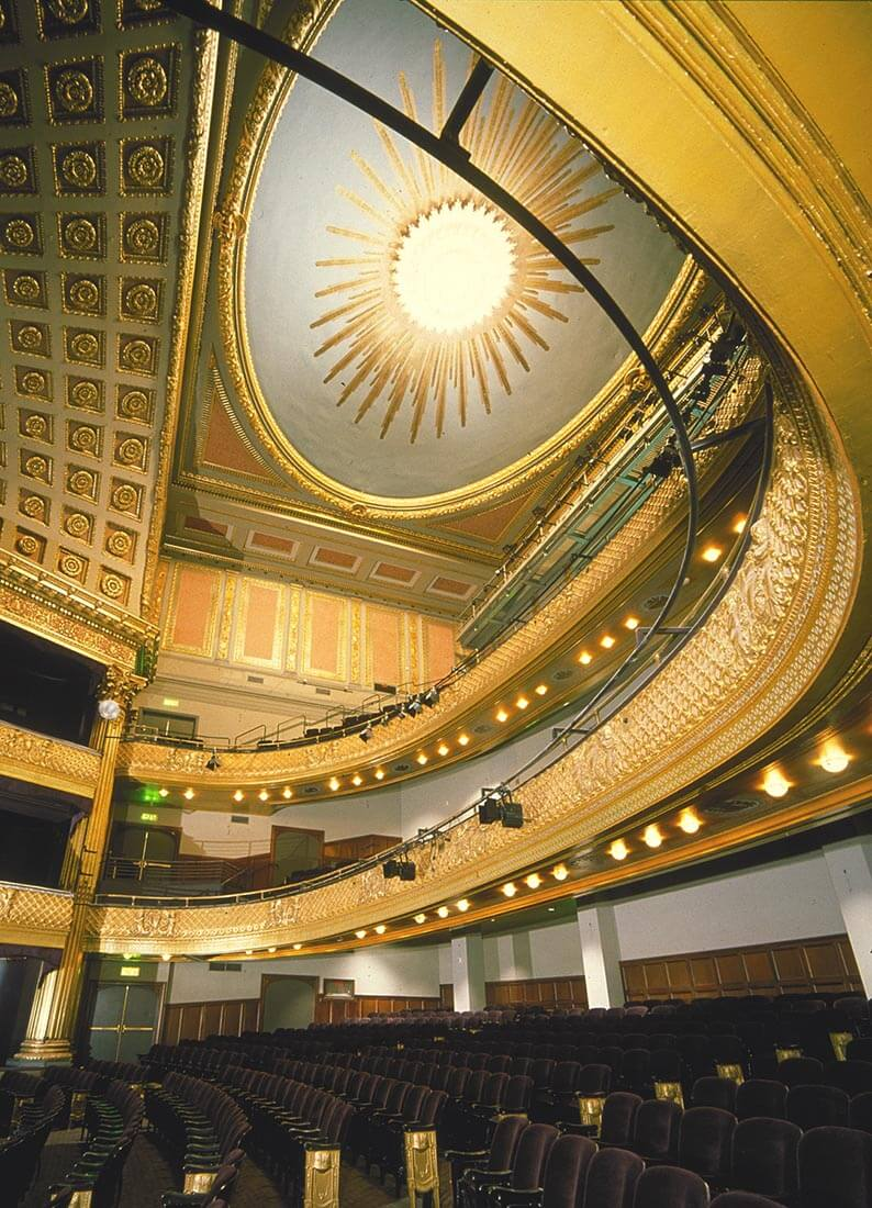 Interior view of lavish Geary Theater in San Francisco, CA with sweeping forms and upholstered seating