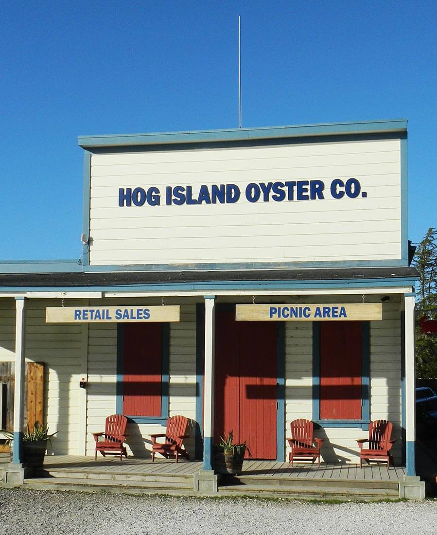 Exterior view of historical wood building with 'Hog Island Oyster Co.' signage above charming wood porch