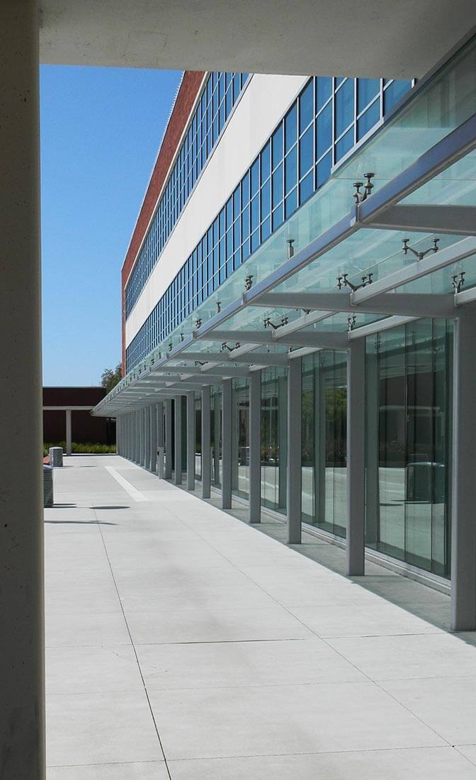Exterior view of Richmond Civic Center in Richmond, CA showing brick and glass facade with covered walkway and adjacent courtyard