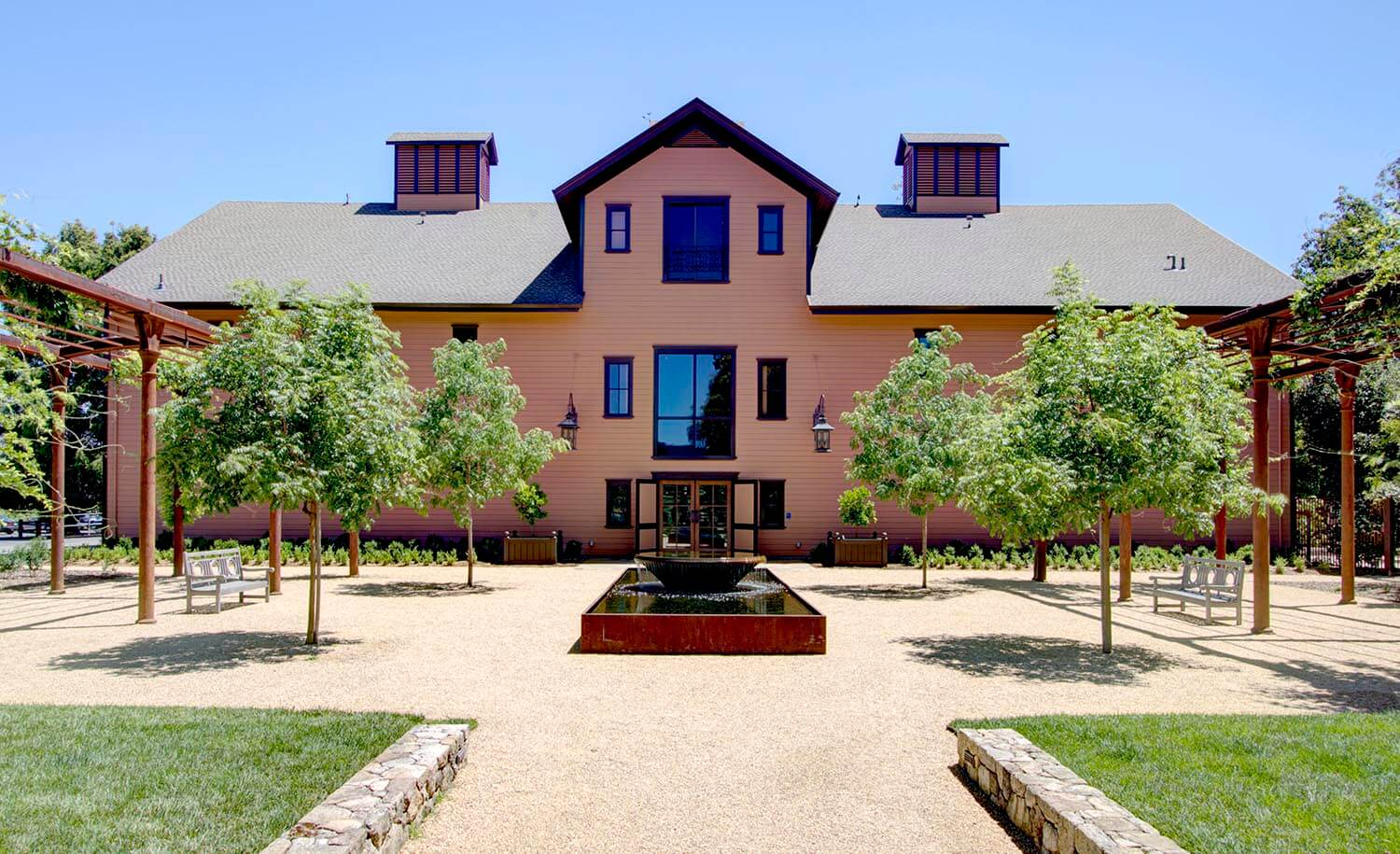 Exterior view of winery building with symmetrical, landscaped courtyard with fountain in foreground