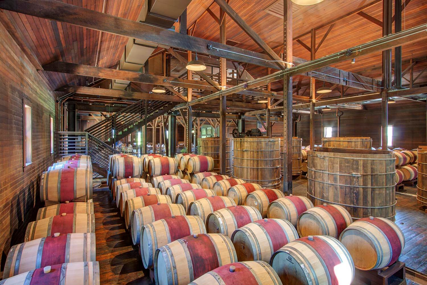 Interior view of wine barrel storage room with wine-stained barrels and other winery equipment