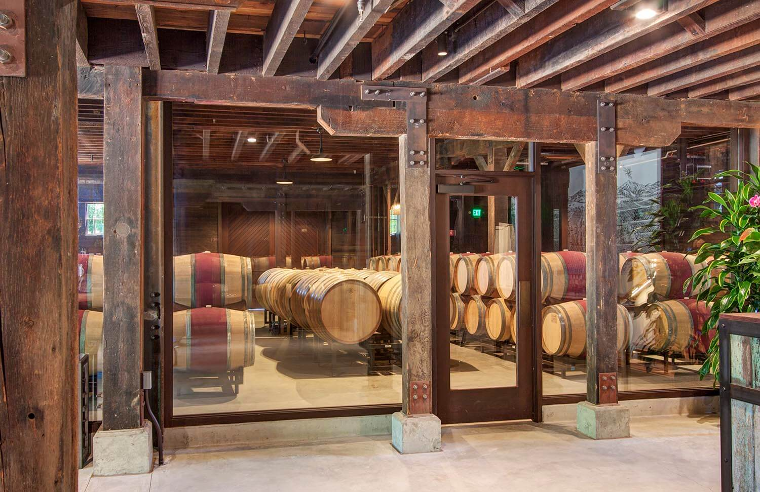 Interior view of wine barrel storage room behind glass walls and closed, glass door